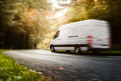 Delivery van drives on a road Photo Credit: Marcus Millo (iStock).