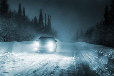 Car driving in forest with headlights lighting snow road Photo Credit: IakovKalinin (iStock).