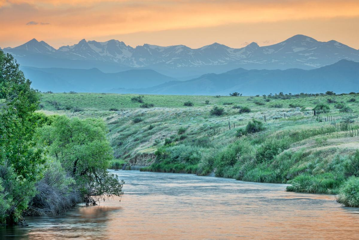 St Vrain Creek and Front Range of Rocky Mountains at dusk, St Vrain State Park near Longmont, Colorado. Photo Credit: marekuliasz (iStock).