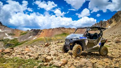 4x4 Side-by-Side off-road vehicle, UTV ATV with a beautiful mountain range in the background near Ouray, Colorado. Yankee Boy Basin. Rocky Mountains.