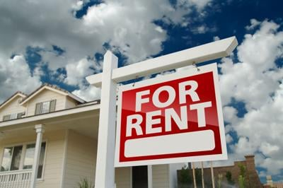 Red and white For Rent sign in front of house Photo Credit: Feverpitched (iStock).
