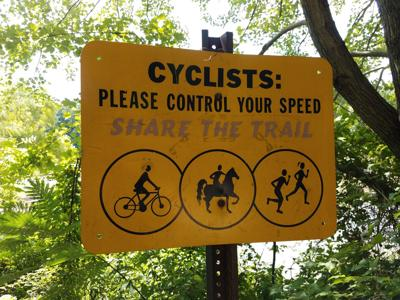 yellow cyclists please control your speed share the trail sign with symbols Photo Credit: Justin Smith (iStock).