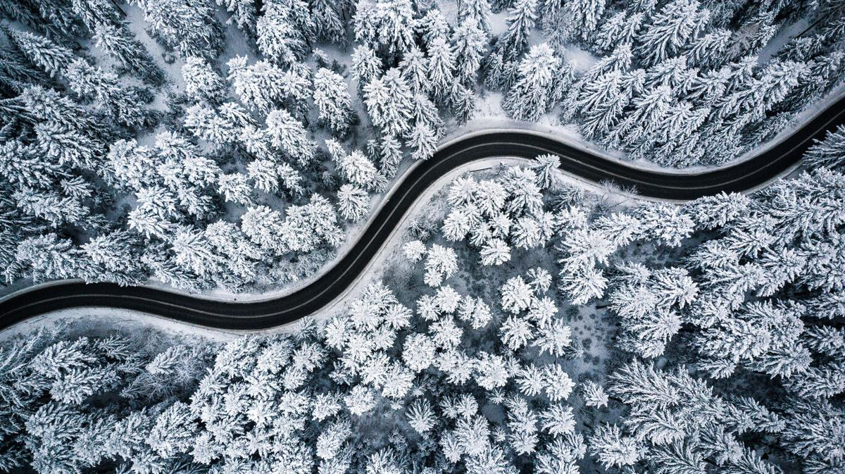 Curvy windy road in snow covered forest, top down aerial view File photo. Photo Credit: merc67 (iStock).