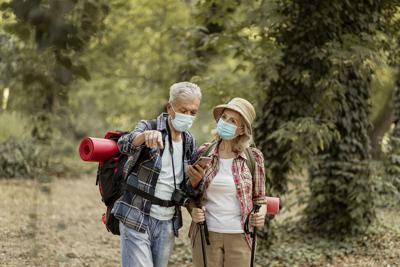 Hikers with masks on File photo. Photo Credit: PixelsEffect (iStock).