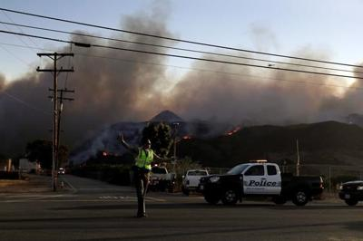 California city reeling from mass shooting besieged by fire