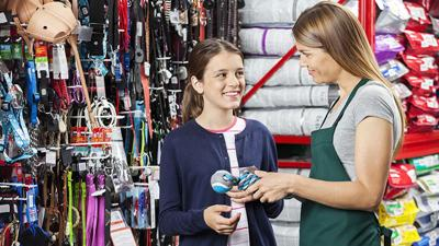 Girl Buying Toy From Saleswoman In Pet Store