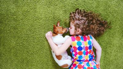 girl cuddling dog stock