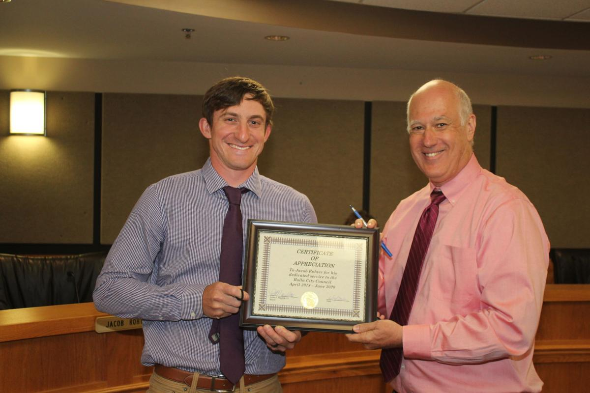 Jacob Rohter accepts a plaque from Mayor Louis Magdits IV