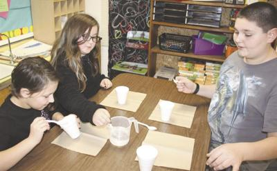 Clopton YMCA students Alaina Henderson, Milly Brown and Joey Dillon create Insta-Snow during a STEM project