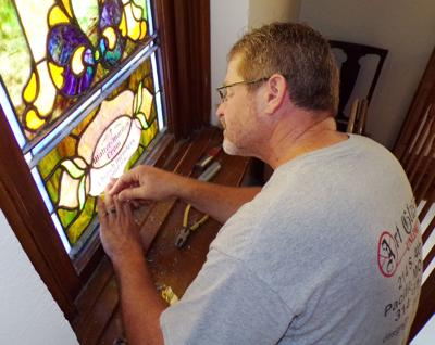 Greg Mowery of Art Glass Unlimited in St. Louis puts the finishing touches on a stained glass window at Clarksville United Methodist Church