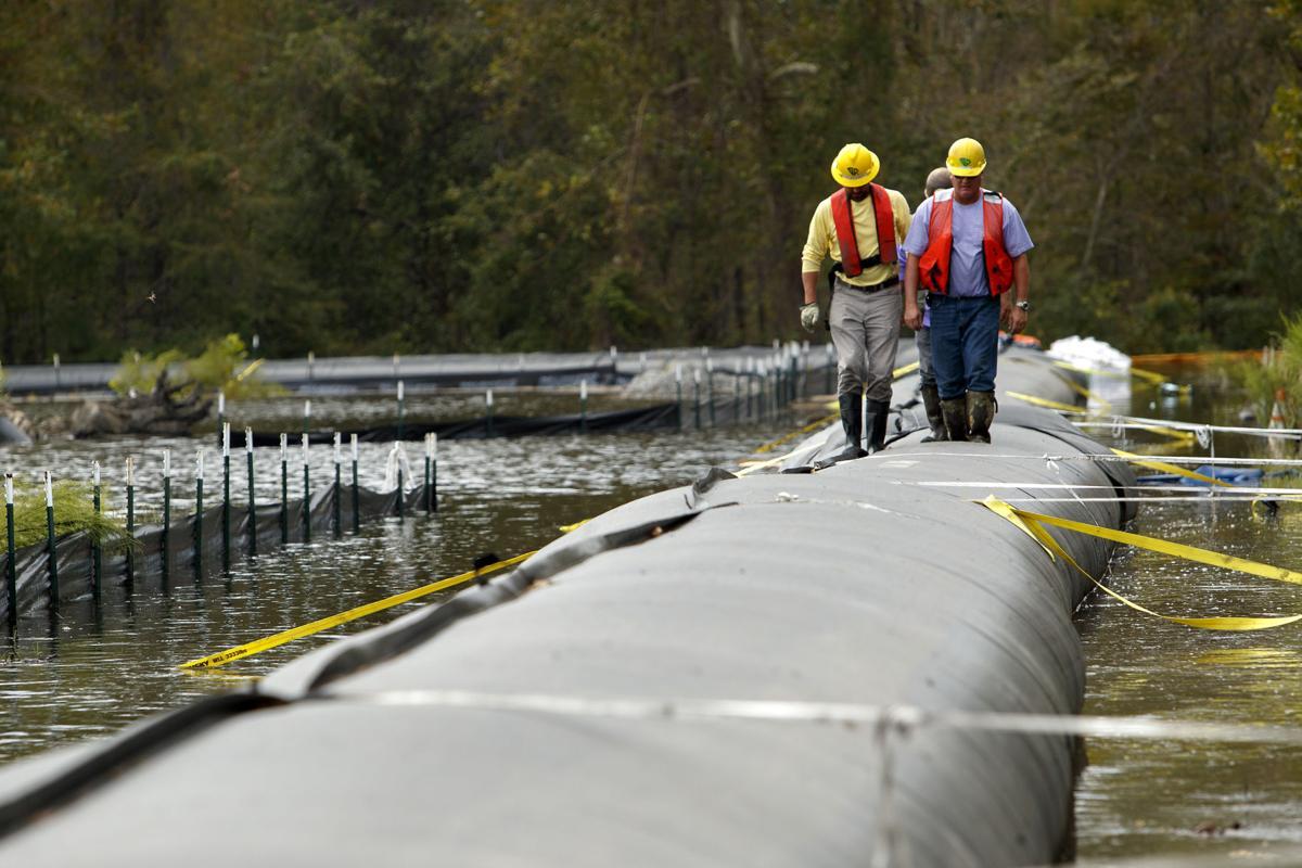 Crew monitor coal ash pit dam