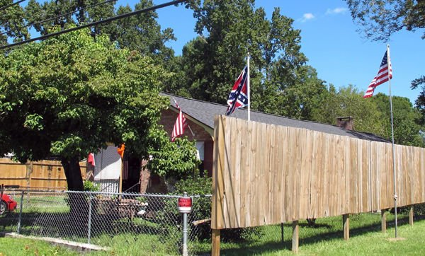Battle over flag goes on: Summerville neighbors of Confederate flag owner build fences, watch flag go higher