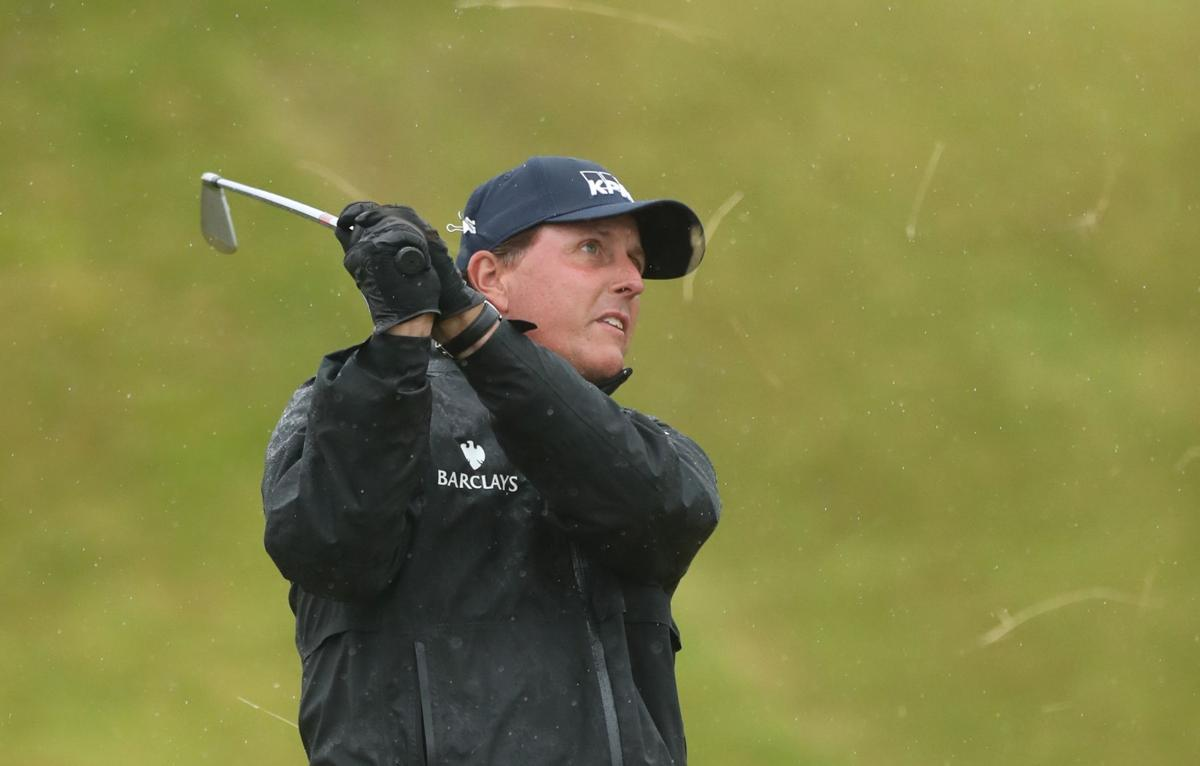 Mickelson shines in wind and rain, keeps Open lead