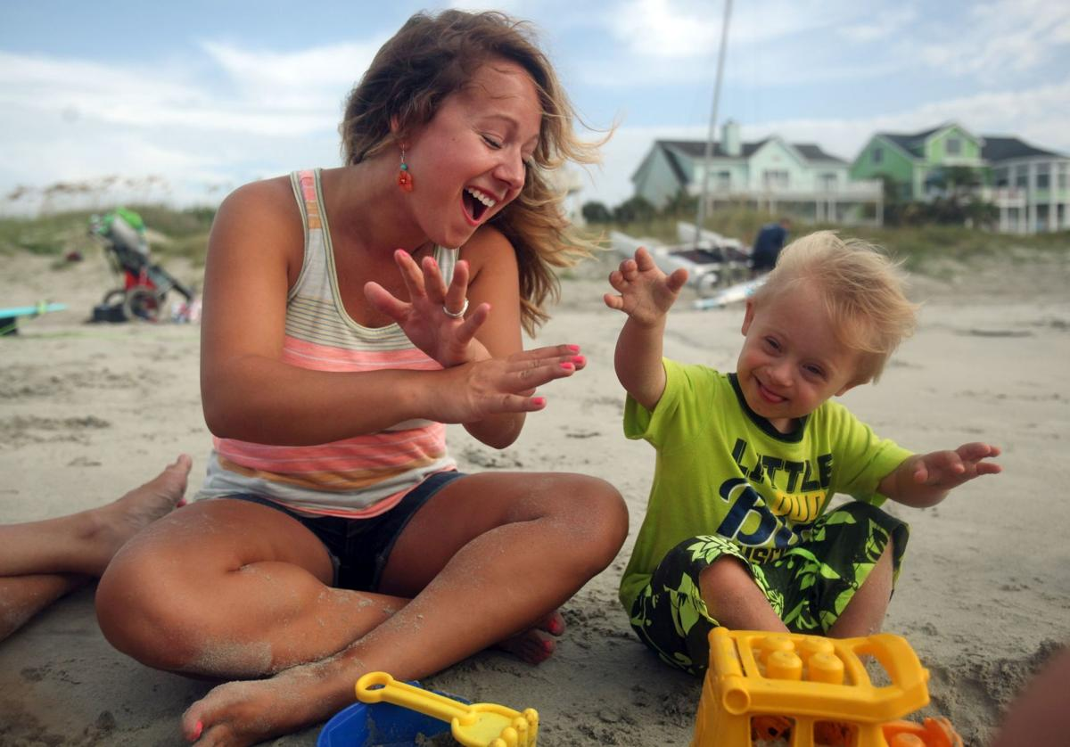 "Nicole Popadich sings ""The Wheels on the Bus"" with her son, Owen, while visiting Isle of Palms in August. Owen, 2, was born with Down syndrome."