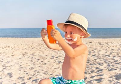 The mustache drawing sunscreen on baby (boy) face. (copy)