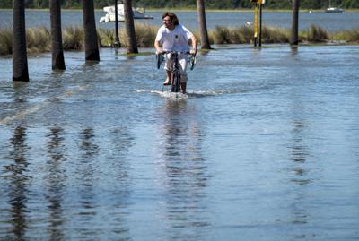 PRINT A cyclist on flooded Lockwood Boulevard Monday.