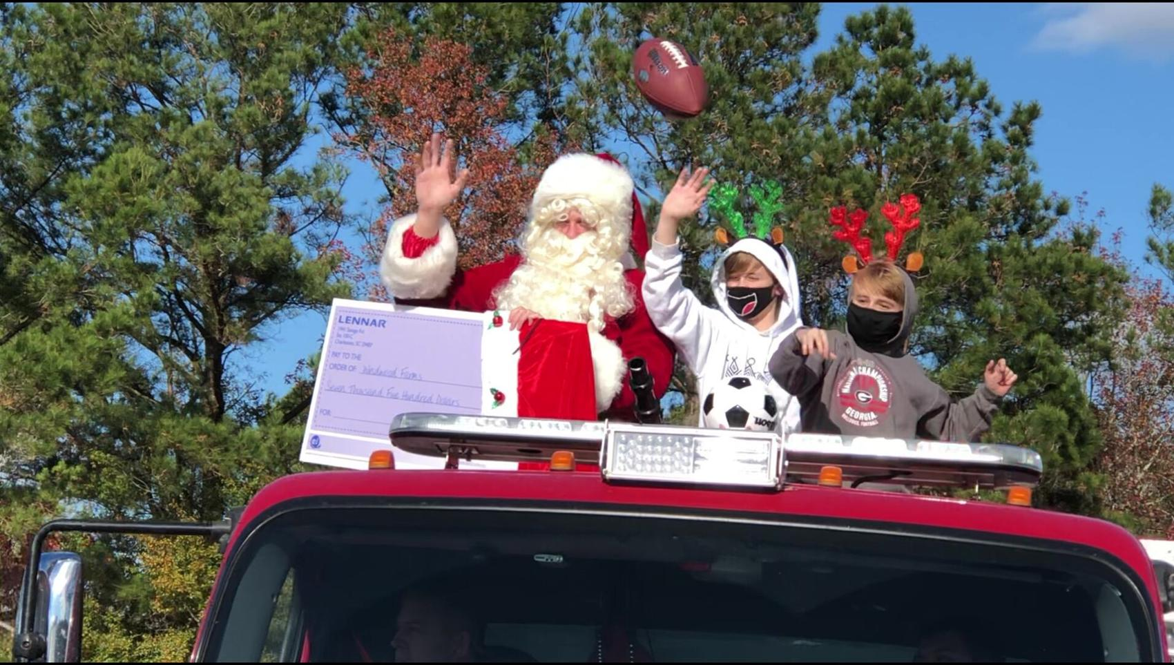 """Jason Byham and Santa and his two """"reindeer helper"""" sons end the Christmas parade at Windwood Farm Home for Children."""