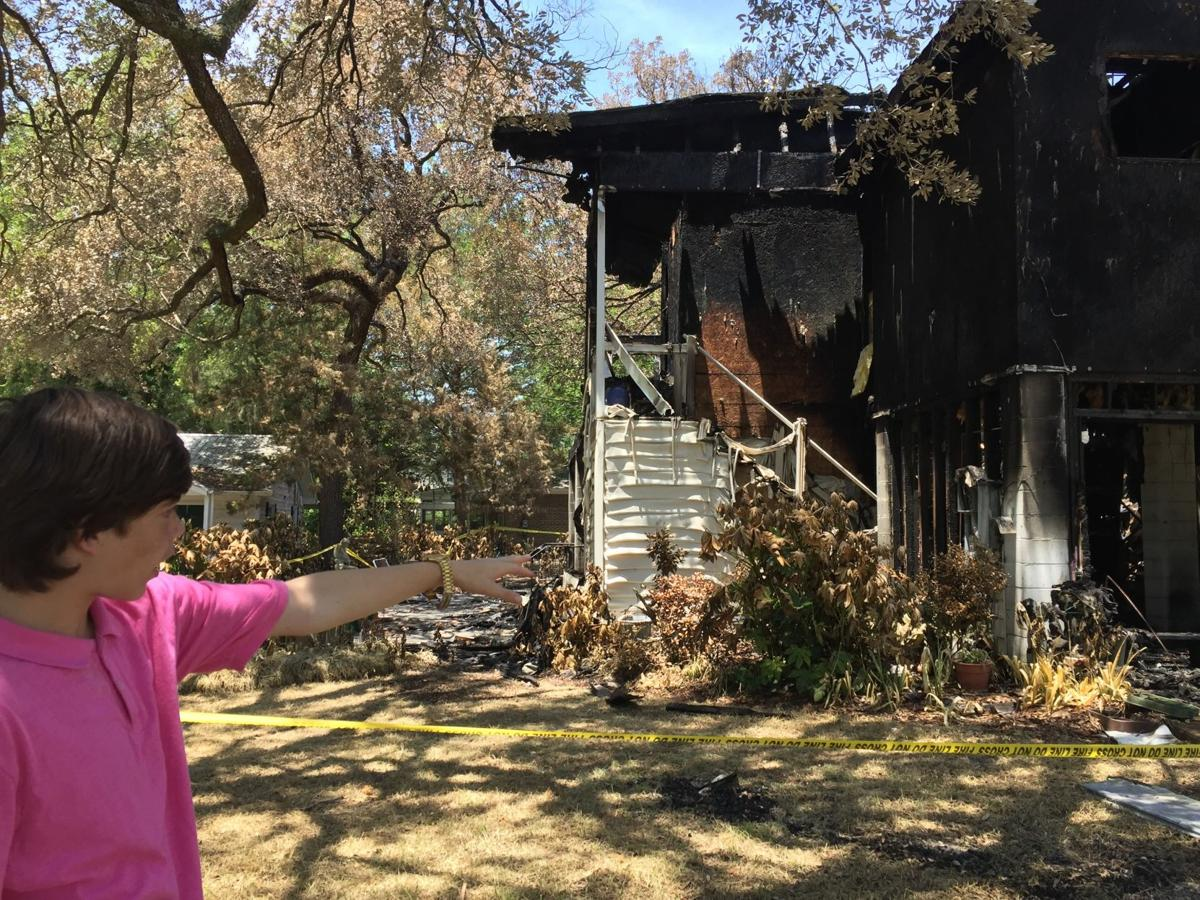 James Brown points to his great-great-aunt's burned out home