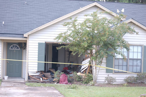 Driver injured after car runs into house