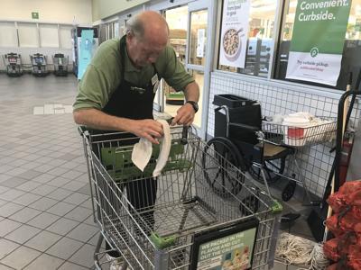 Publix employee wiping down shopping carts