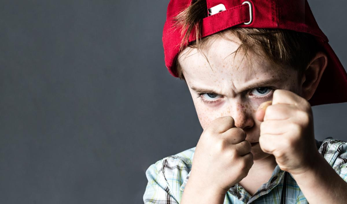 threatening boy with freckles and red hat back looking violent