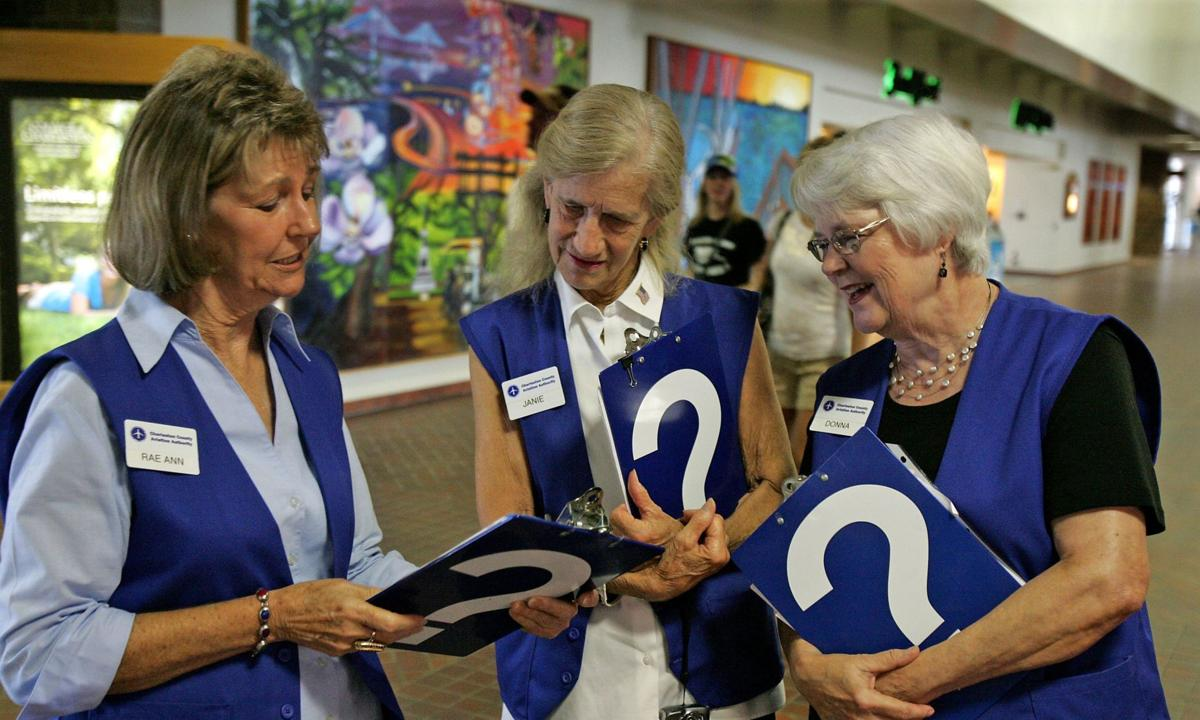 Airport greeters Volunteers answer passengers' questions