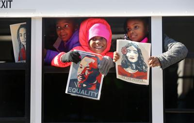 MLK parade kids on bus with posters