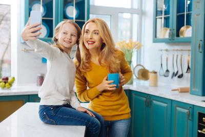 Cheerful mother and daughter taking selfies