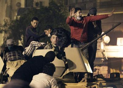Mubarak fires Cabinet, but protests rage on