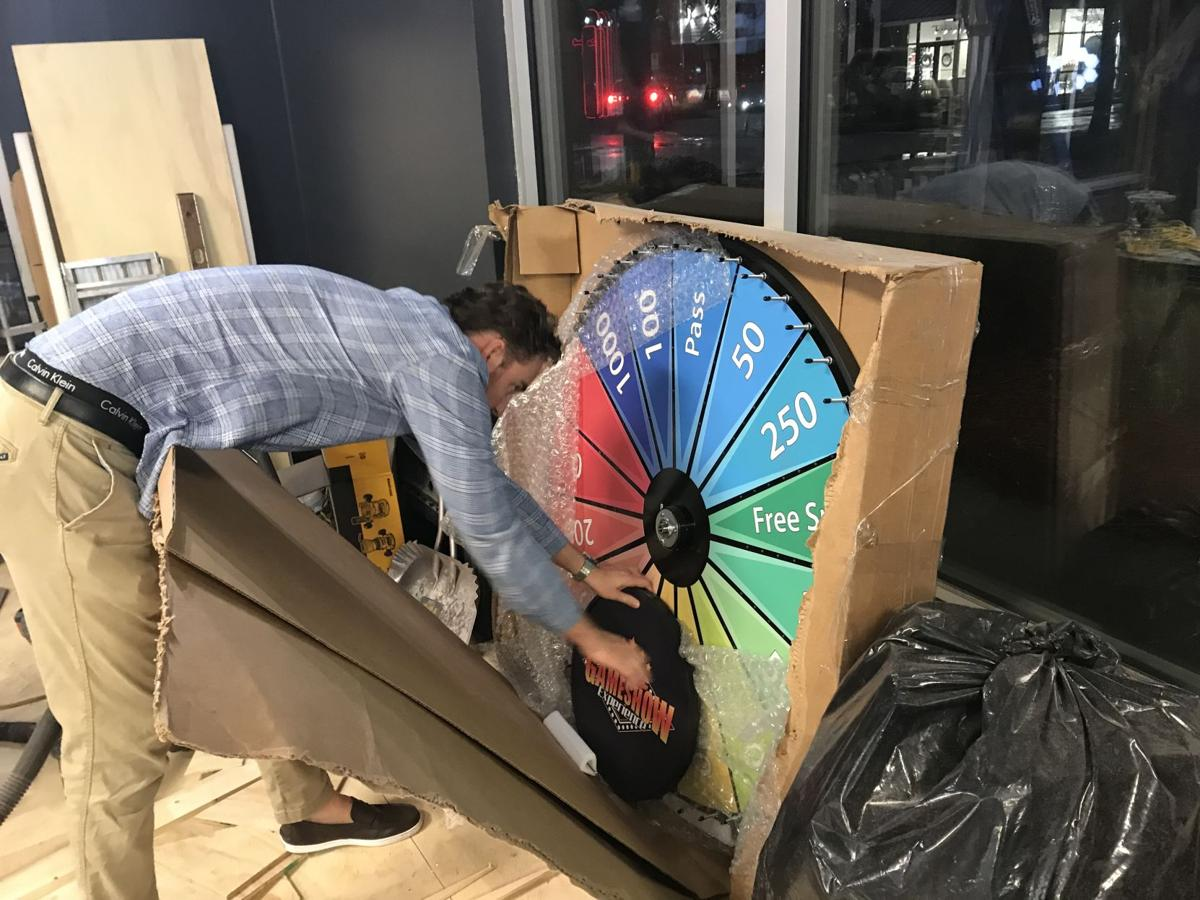 Game Show owner Jason Pap unboxing a wheel for the new entertainment venue