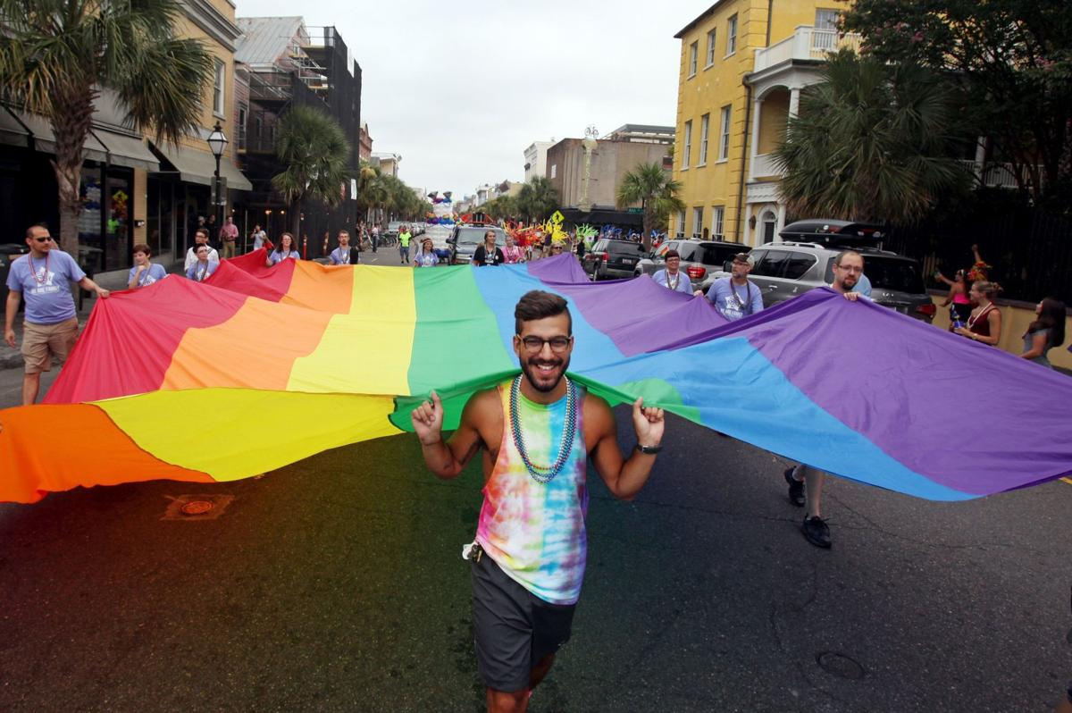 Pride Parade dude with flag back broad