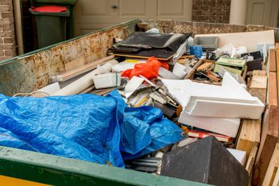 Skip bin full of household waste rubbish on the frond yard. House clean up concept