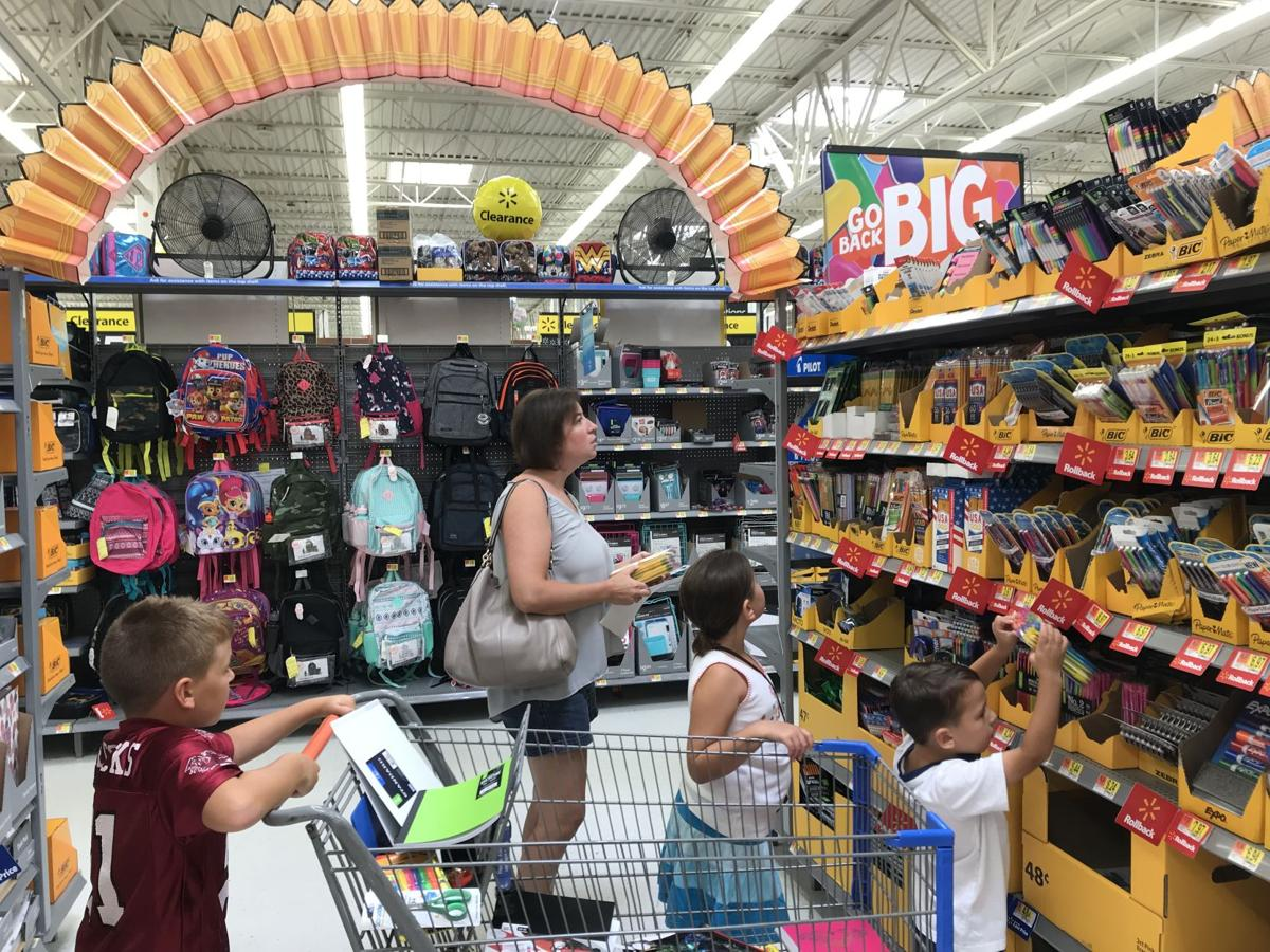 Walmart back-to-school shopper with three children looking at pencils