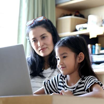 Mother helping child laptop