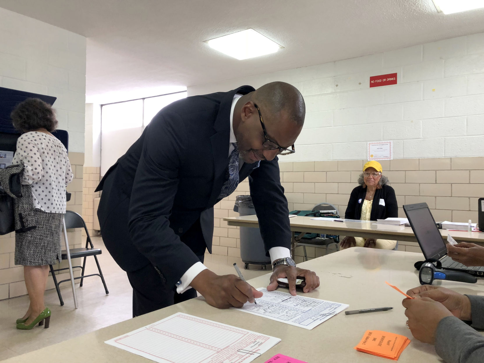 Byron Gipson signs in to vote during