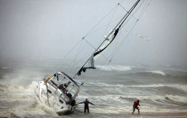 Irene churns up coast, weaker but still ferocious
