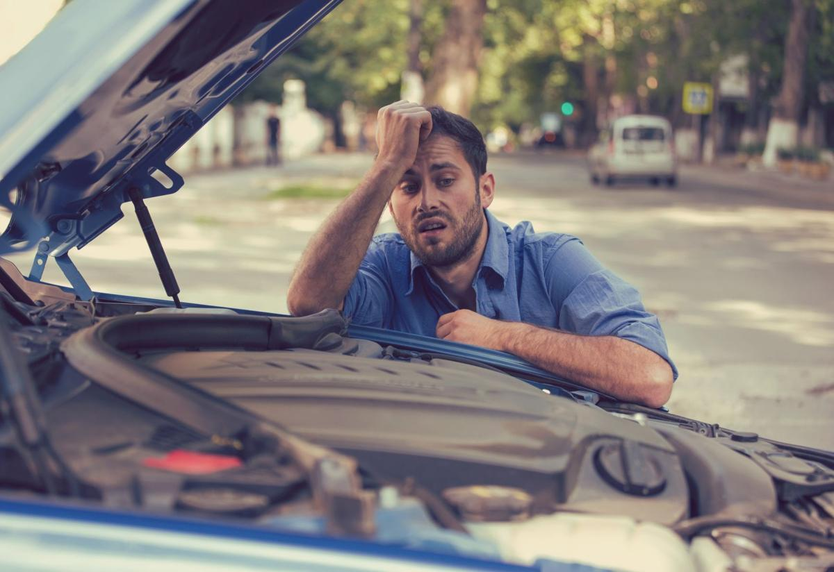 stressed man having trouble with broken car looking in frustration at failed engine