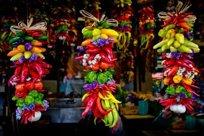 Colorful bunched hanging hot and sweet peppers at market