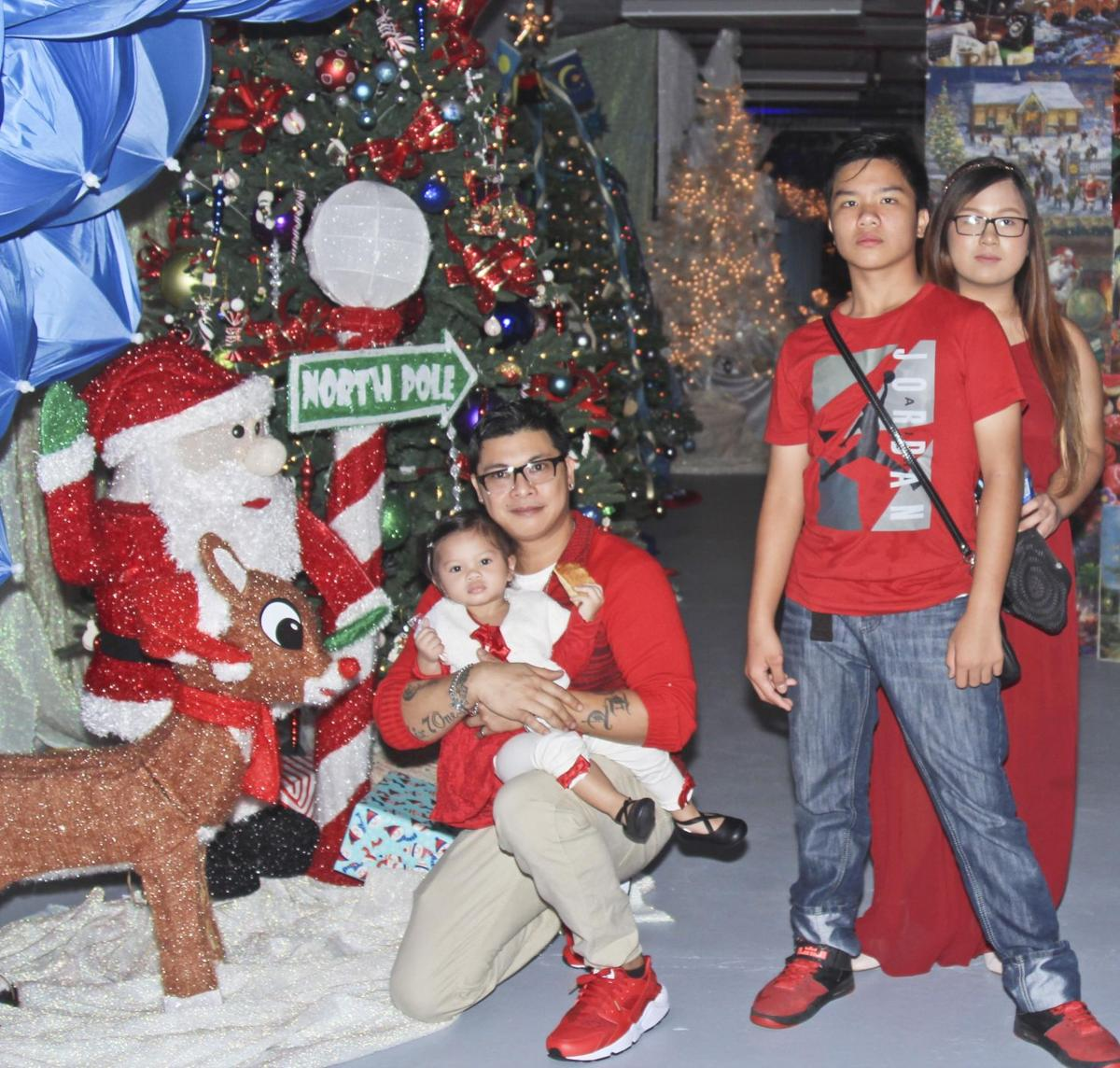 jerry solangon kneeling poses for a photo with family at the christmas dream display on dec 1 the christmas themed display located on the second - A Dream For Christmas