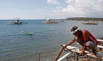 A fisherman repairs his boat overlooking fishing boats that fish in the disputed Scarborough Shoal in the South China Sea, at Masinloc, Zambales, in the Philippines