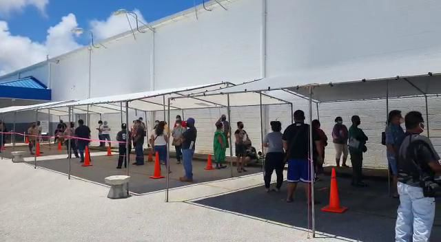 Taxpayers line up under canopies at income tax line