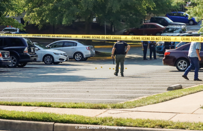 Police officers investigate a shooting on Yosomico Drive