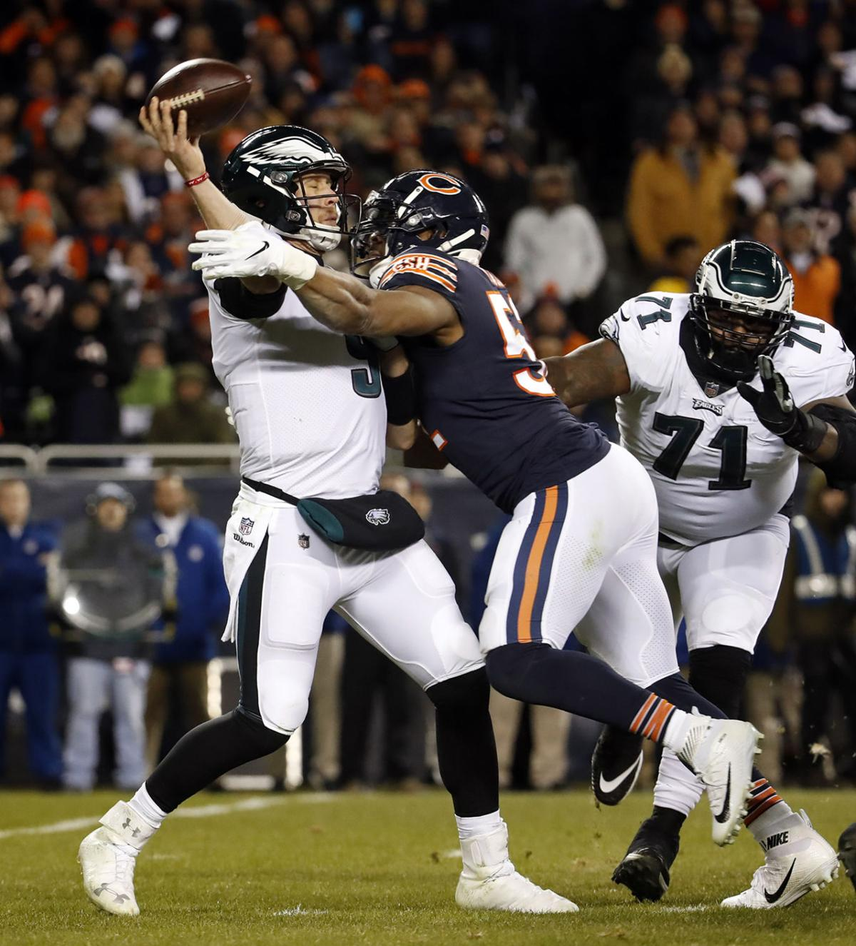 Philadelphia Eagles quarterback Nick Foles (9) gets a pass off as he's hit by Chicago Bears outside linebacker Khalil Mack (52) in the fourth quarter during the NFC Wild Card game on Sunday, Jan. 6, 2019 at Soldier Field in Chicago, Ill. The Eagles beat the Bears, 16-15.