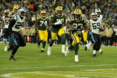Aaron Jones (33) of the Green Bay Packers scores a touchdown against the Carolina Panthers in the game at Lambeau Field on November 10, 2019 in Green Bay, Wisconsin.