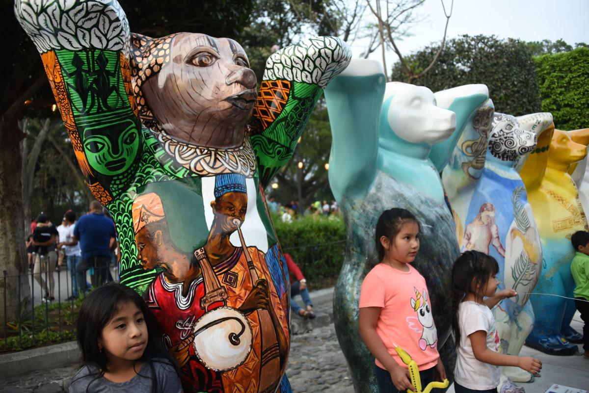 """Guatemalans visit the itinerant exhibition """"United Buddy Bears, The Art of Tolerance"""" at the Plaza Mayor Antigua Guatemala, 45 km West of Guatemala City on April 28,2019. - Each of the 144 two-meter-high colorful bears represents a UN member country."""