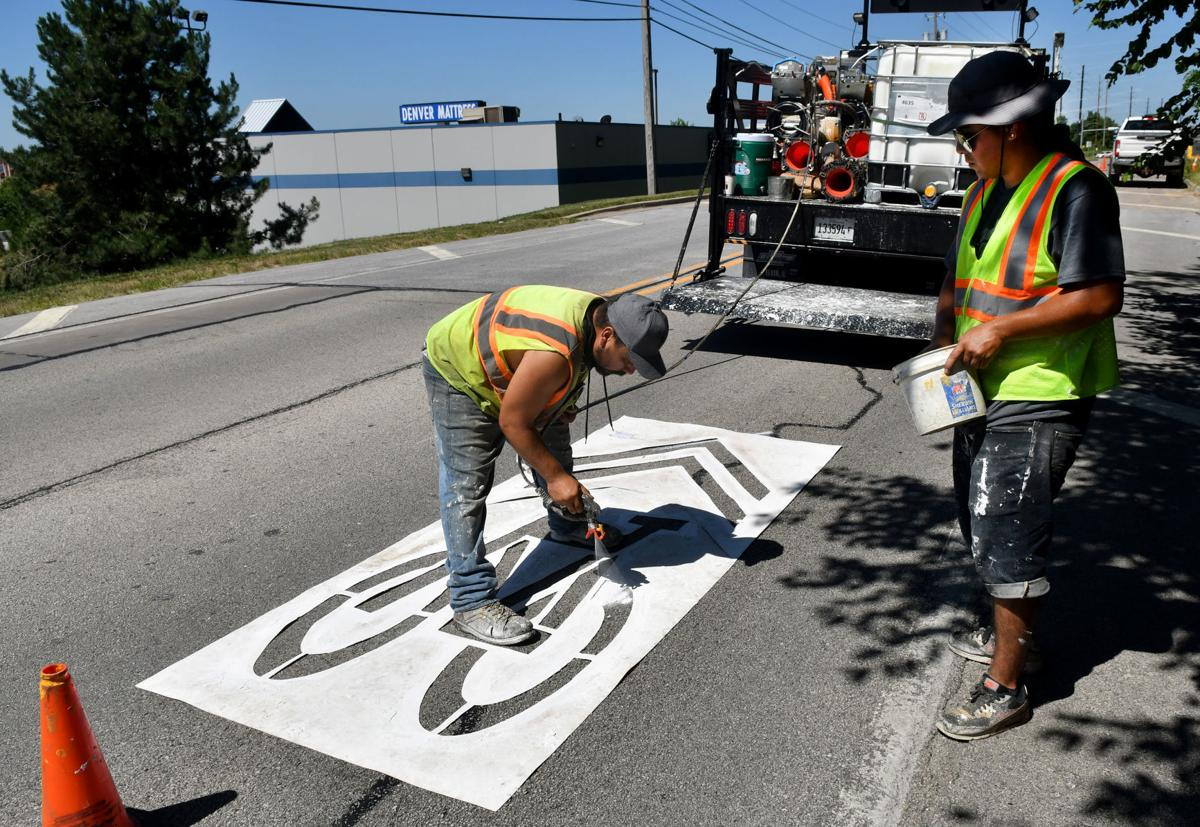 Painting of sharrows for bike lanes in Moline.