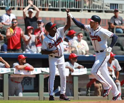 Atlanta Braves' Freddie Freeman gets five from third base coach Ron Washington after hitting a two-run home run to give the Braves a 2-0 lead over the St. Louis Cardinals during the fourth inning on Wednesday, Sept. 19, 2018 in Atlanta, Ga.