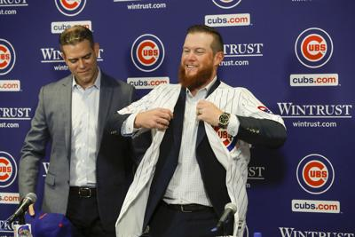 New Chicago Cubs pitcher Craig Kimbrel puts on his new jersey after being introduced by Chicago Cubs President Theo Epstein at Wrigley Field in Chicago on June 7, 2019.