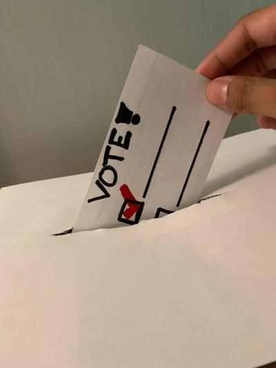 Image of a vote being cast in a ballot box