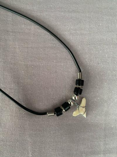 A shark tooth necklace purchased through the Etsy app